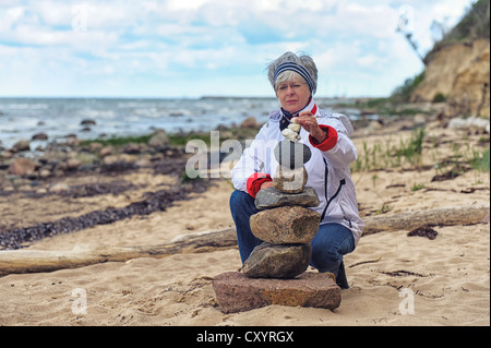 Woman building a cairn on the beach, Timmendorf on the Island of Poel, Mecklenburg-Western Pomerania - Stock Photo
