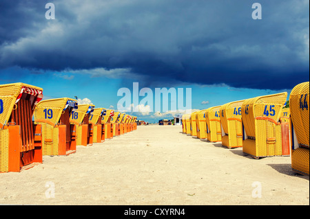 Two rows of yellow roofed wicker beach chairs in the sunshine, dark rain clouds at the back, Mecklenburg-Western - Stock Photo
