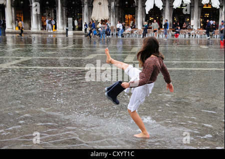 A young girl plays with the water flooding St. Mark's Square during the first day of the 'Acqua Alta' season in - Stock Photo