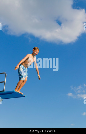 Boy jumping from the three-metre diving board at an outdoor swimming pool - Stock Photo