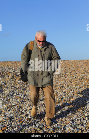 Elderly man walking carefully on pebble beach - Stock Photo
