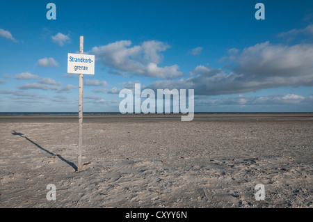 Sign, lettering 'Strandkorbgrenze' on the beach of St. Peter-Ording at low tide, wicker beach chairs must not be - Stock Photo