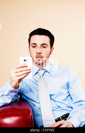 Young manager sitting on a sofa with his smartphone and checking an SMS - Stock Photo