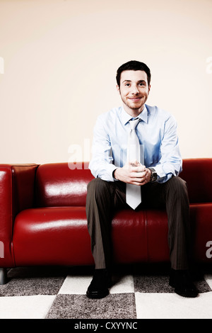 Young man sitting on a sofa, smiling and waiting - Stock Photo