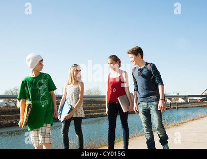 Four teenagers going for a walk along the Rhine River, Mannheim, Baden-Wuerttemberg - Stock Photo