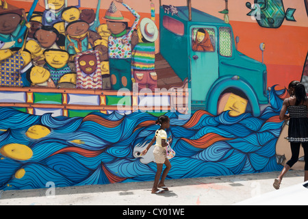 A black woman and girl walk past street art of a truck of people in Wynyard, Maimi, USA. Faces on the truck illustrate - Stock Photo