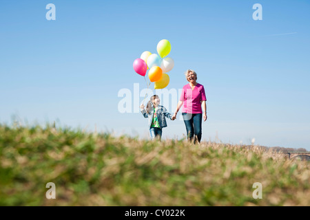 Girls holding balloons in her hand while walking with her mother across a meadow - Stock Photo