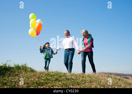 Girls holding balloons in her hand while walking with her grandparents across a meadow - Stock Photo