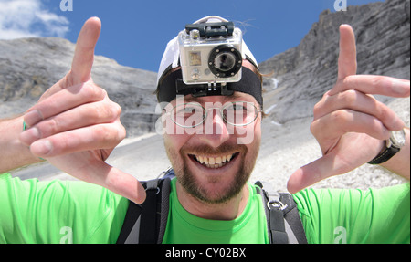 Young man, mountain hiker with a GoPro HD Video Camera mounted to his head, Karwendel Mountains National Park, Tyrol, Austria