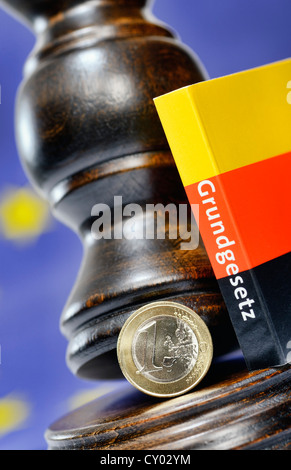An one-euro coin, a judge's gavel and a German constitution, symbolic image for the German Federal Constitutional - Stock Photo