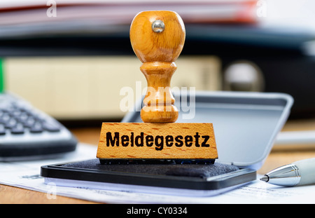 Rubber stamp with the wording 'Meldegesetz', German for registration law, on a desk - Stock Photo