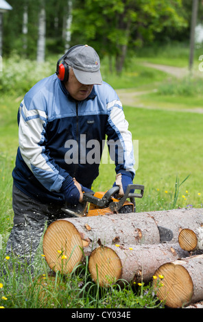Elderly man cutting a spruce log with a chainsaw , Finland - Stock Photo