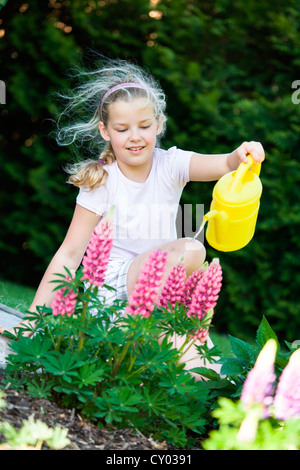 Girl with a watering can in the garden - Stock Photo