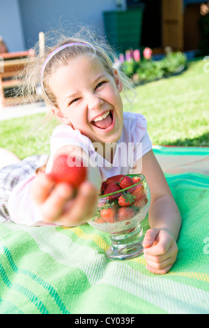 Laughing girl with strawberries in the garden - Stock Photo