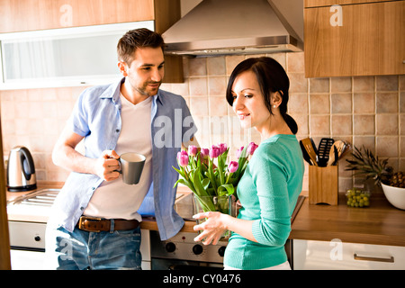 Young couple with a bunch of tulips in the kitchen - Stock Photo