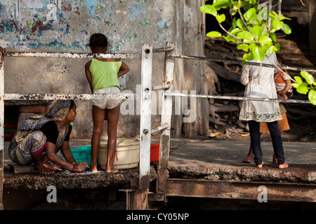 Mother and Girl doing Laundry on the River Banks in Kolkata, India - Stock Photo