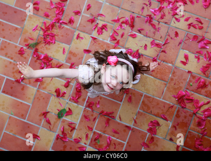 Little girl, three years, dancing on red petals, from above - Stock Photo