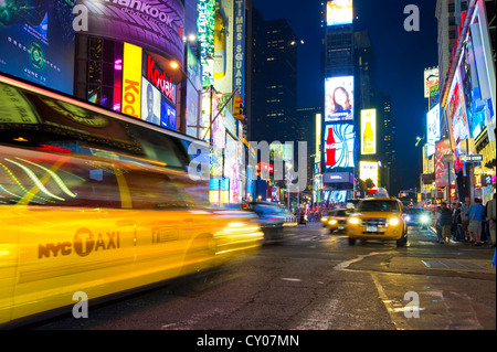 Taxi with motion blur in Times Square, night scene, Manhattan, New York, USA - Stock Photo