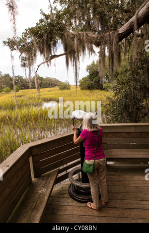 Elderly woman uses a binocular viewer on salt marsh boardwalk at Honey Horn Plantation on Hilton Head Island, SC - Stock Photo
