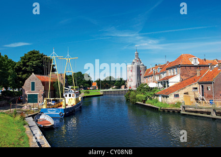 Netherlands, Enkhuizen, Classic Dutch vessels in the canal, Drommedaris Tower in the background. - Stock Photo