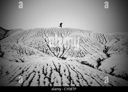 Male figure running across snowy landscape - Stock Photo