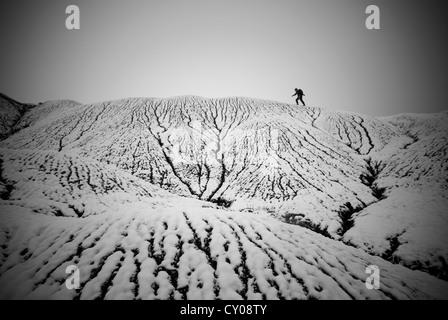 Male figure walking across snowy landscape - Stock Photo