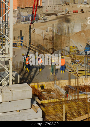 Large construction site, workers pouring concrete into an area surrounded by boarding and reinforcements, North - Stock Photo