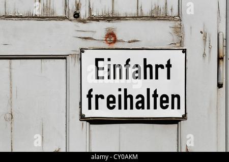 Sign lettering 'Einfahrt freihalten', German for 'Keep driveway clear', on an old wooden gate, PublicGround