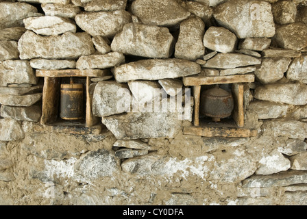 A unusual pair of Prayer wheels are imbedded in a stone wall at the Village of Nako, in the Kinnaur district of - Stock Photo