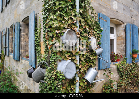 Zinc tubs and watering cans on an ivy-covered old-Frankish house, Simonshofen, Middle Franconia, Bavaria - Stock Photo