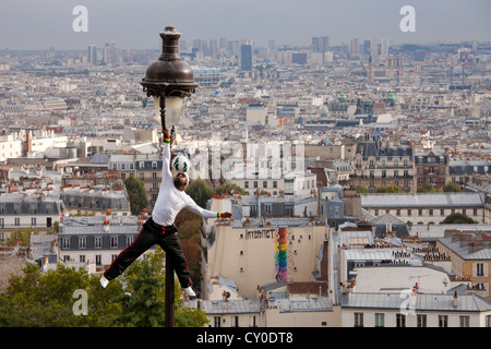 acrobatic performance artist at an old street lamp on the hill of Sacre Coeur and view of Montmartre and Paris - Stock Photo