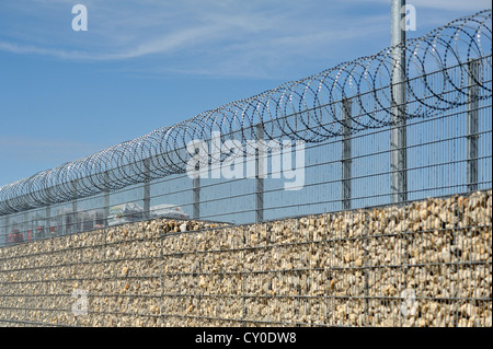 Noise barrier and safety fence with barbed wire in front of the storage yard of a building centre, Eckental, Middle - Stock Photo
