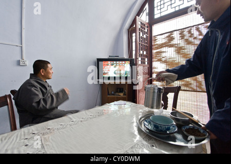 Shaolin Monk Shi De Jian watches TV while tea is being prepared at the San Huang Zhai Monastery on the Song Mountain, - Stock Photo