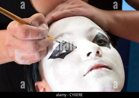 Hands painting the eyes of a pierrot clown - Stock Photo