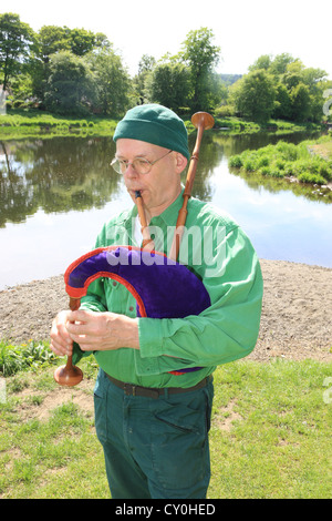 Julian Goodacre a Bagpipe maker in Peeples Scotland playing the pipes outside, outside his workshop. - Stock Photo