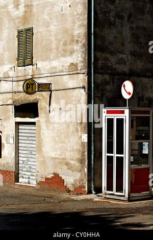 Italian telephone box and postal sign on wall, Canneto, Tuscany Italy - Stock Photo