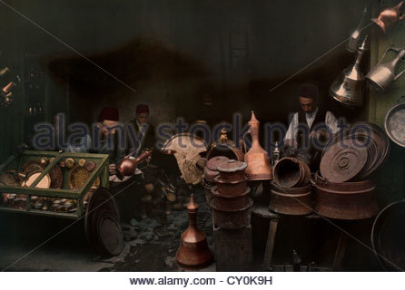Islamic coppersmiths work in a bazaar shop; their wares on display. - Stock Photo