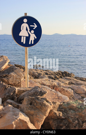 Woman and child walking direction - seaside path traffic sign - Stock Photo