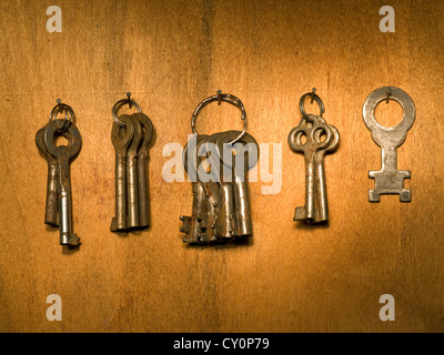 Bunches of old keys on a wooden wall surface. - Stock Photo