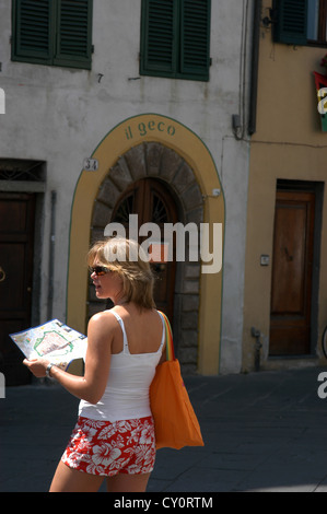 A female tourist in shorts and white top carrying an orange handbag looks for direction from a street map on a street - Stock Photo