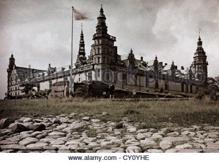A view of the Kronborg Castle on a hill, flag waving in the wind. - Stock Photo