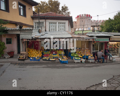 Streets in the Tophane district of Bursa Turkey shop selling fruit and men relaxing and talking - Stock Photo