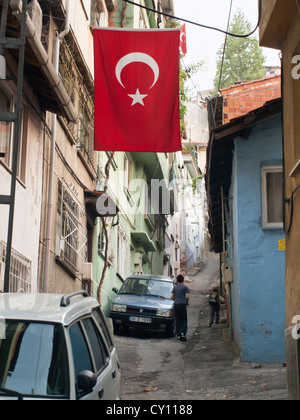 Streets in the Tophane district of Bursa Turkey, Turkish flag waving in an alley - Stock Photo