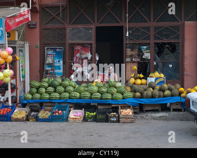 Streets in the Tophane district of Bursa Turkey, female vendor selling melons - Stock Photo