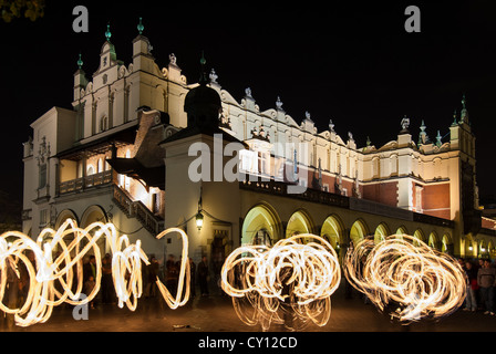 A group of jugglers present a fire show near the Cloth Hall at the Main Market Square on October 27, 2006 in Krakow, - Stock Photo