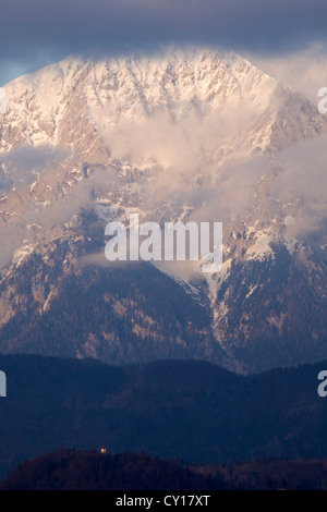 A church sits on a small hill in the shadow of the mighty Kocna mountain peak, Kamnik Alps, Slovenia. - Stock Photo