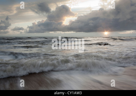 incoming tide at sunset - Stock Photo