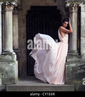 Young woman wearing a long party dress standing in an entrance to a grand building - Stock Photo