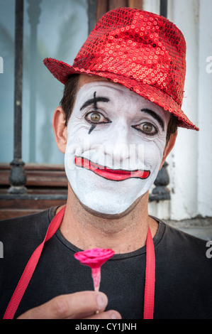 A portrait of a clown street performer in Las Palmas Gran Canaria Spain wearing a red hat with white face, holding - Stock Photo