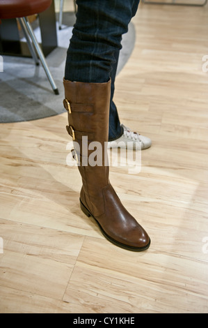 A female person trying on a pair of brown boots in a shop - Stock Photo